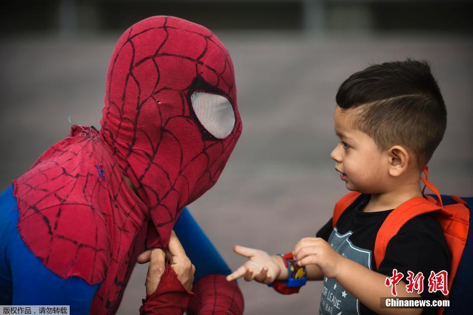 朋友跟一名扮演蜘蛛侠的演员交谈.他比划的手势似乎在询问,蜘蛛