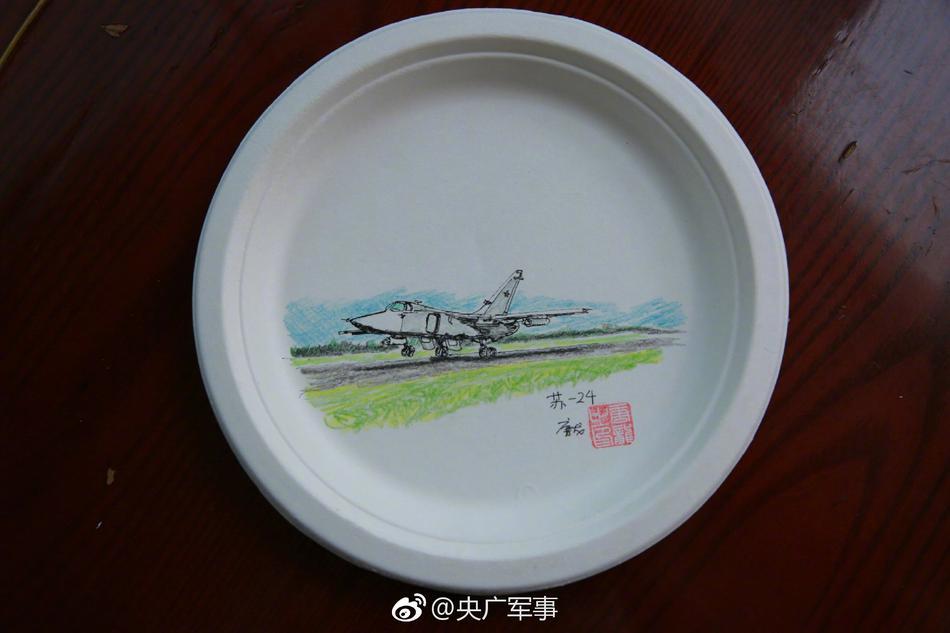 吴志峰正坐在一堆画纸和盘子前进行创作