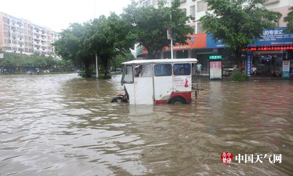 14日,广西桂林临桂区一辆三轮车停在水中无法前行,车上乘客着急无