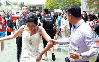 华大泼水节新人拍婚纱照被泼湿身