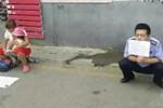 女子抱小孩坐医院乞讨 保安蹲地上举牌揭骗