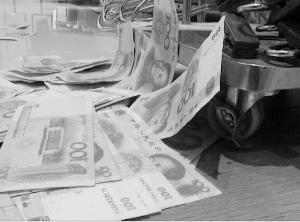 女子撤在地上的钱。信息时报记者 巢晓 摄