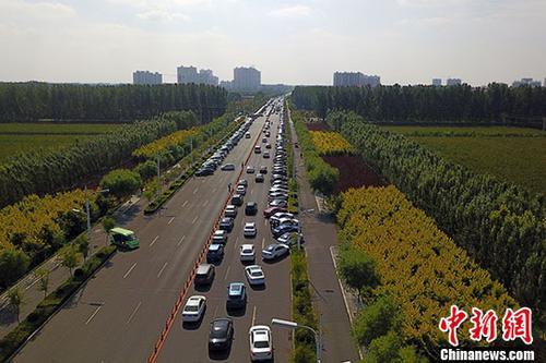 资料图:安新县崇文大街两侧停满前来旅游的车辆。 中新社记者 韩冰 摄