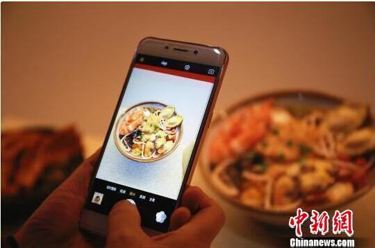柳州螺蛳粉博物馆里,吸引游客用手机拍摄螺蛳粉仿真模型。 资料图 摄