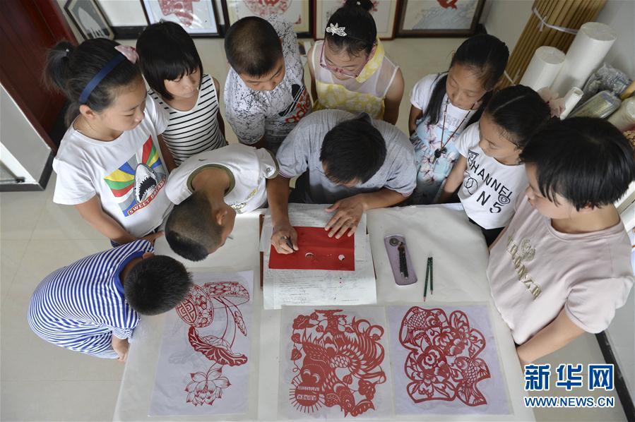 中)身旁,学习剪纸技艺.今年暑期,河北省南宫市民间艺人任书恒