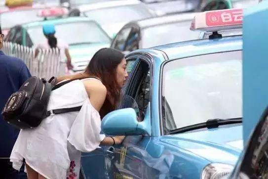 一位女乘客在车窗咨询司机能否前往要到达的目的地。图/新快报