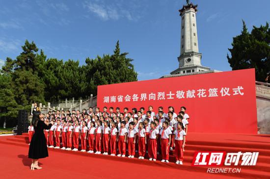 少先队员们在烈士纪念塔下唱响《我们是共产主义接班人》。