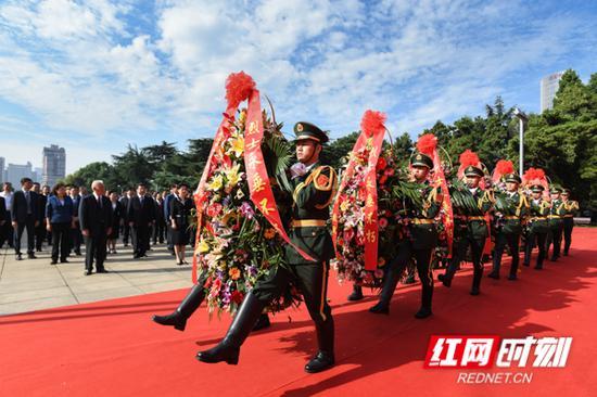14名礼兵抬起花篮,缓步走向革命烈士纪念塔,将花篮敬放在纪念塔前。
