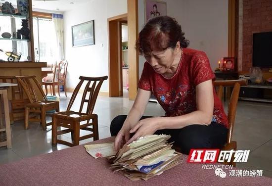 """(妻子吴春英翻看着""""老姜""""在部队时,写给家里的一封封书信。)"""