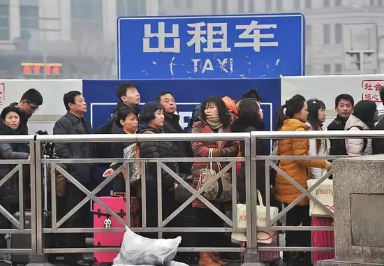 火车站、机场外的出租车候车处,往往大排长龙。图/新华社