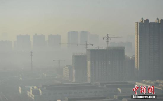 资料图:一处在建楼盘被雾霾笼罩。 中新社记者 翟羽佳 摄
