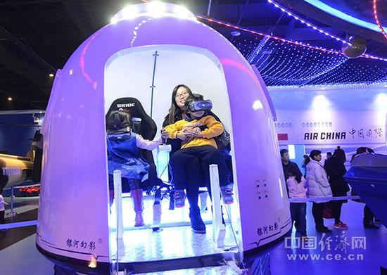资料图片:观众在航空航天科技体验馆里体验载人航天器的返回舱。(图片来源:视觉中国)
