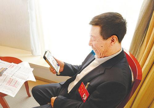 ▲北京:沙万里代表与繁峙县小砂河村村民视频通话。   本报记者李联军摄