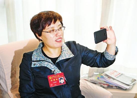 北京:吴秀玲代表与右玉县大南山植树造林工地现场的干部群众视频通话。记者李联军摄