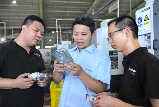 张仕恒在车间,和工友们钻研讨论业务。