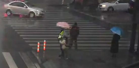 ▲女孩为执勤警员撑伞 视频截图