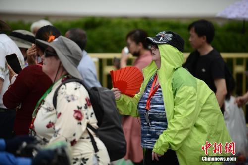 """5月22日,在天安门前游玩的外国游客""""花式""""遮阳。 中新社记者 张兴龙 摄"""