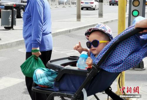 5月22日,北京街头一名孩子在婴儿车中戴着墨镜。中新社记者 杜洋 摄
