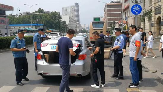 2018年8月1日上午,济南火车站,一辆注册某网约车平台的轿车被执法人员拦下接受检查。图/大众网潍坊
