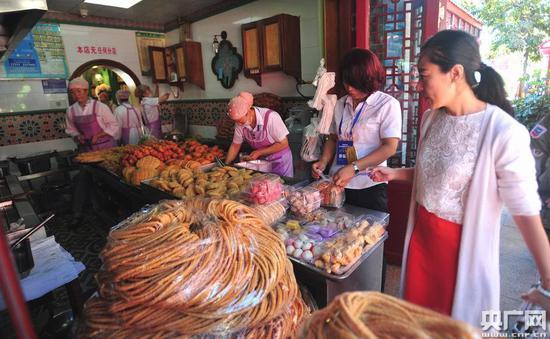 游客正在购买新疆特色美食糕点(记者罗成摄)