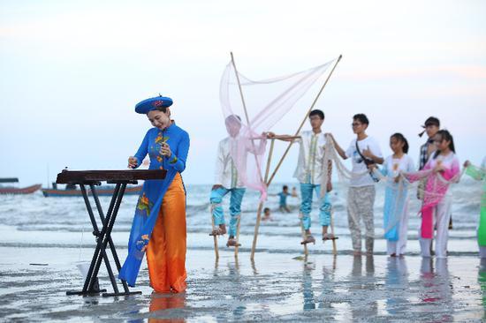 阮美霞(左一)在海边弹奏独弦琴。采访对象供图