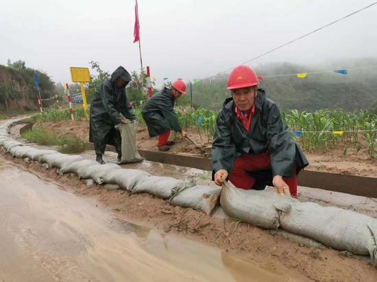图为北京管道陕西处员工在防汛现场设置临时挡水墙