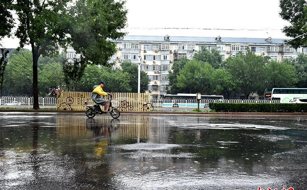 北京遇今年汛期最强降雨 市民冒雨出行