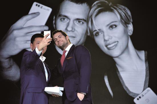 (华为消费者业务CEO余承东与P9手机形象代言人、好莱坞影星亨利·卡维尔在P9全球发布会上合影)