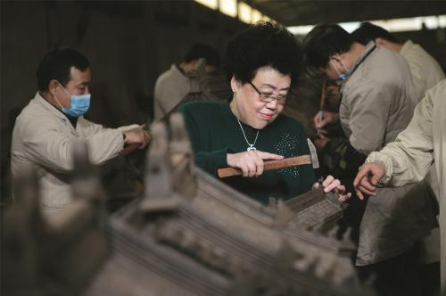 陈丽华女士示范安装影壁上的吞脊兽。中国紫檀博物馆供图