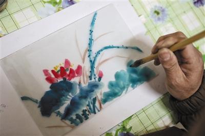 1月29日,北京宫灯技艺传承人郭燕青在画宫灯。