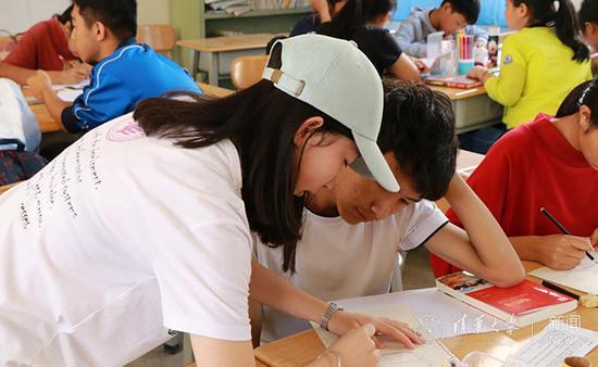 队员指导学生制作手抄报并交流阅读感悟。