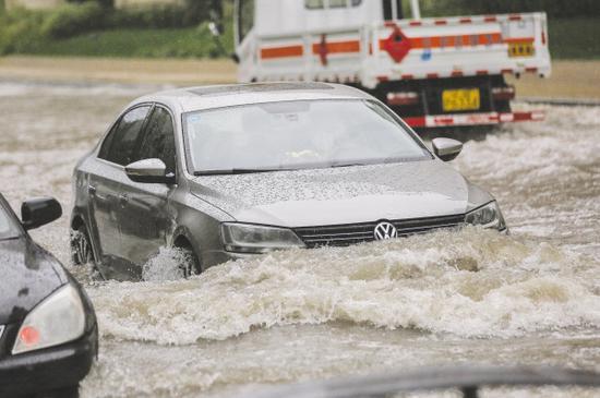 低洼区域出现积水,车辆涉水通过。图/高强