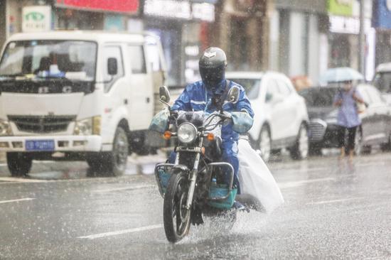 一名送餐员冒雨送餐。图/高强