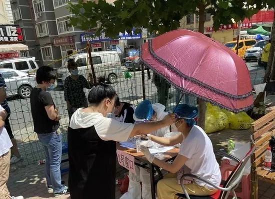 ▲热心居民,为沙河口区幸福社区工作者打伞遮阳。