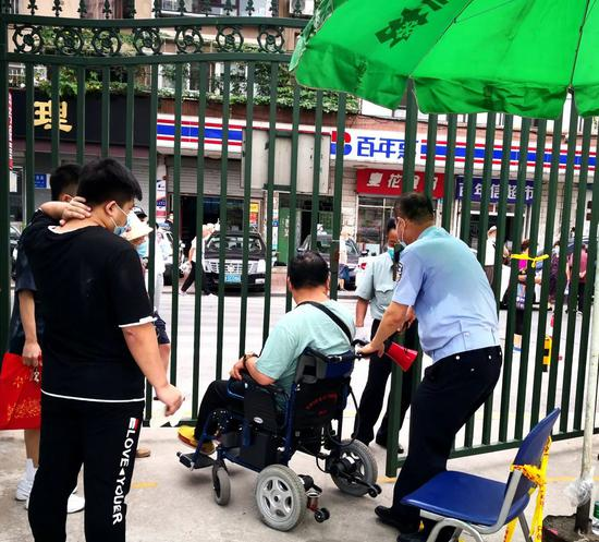 ▲春柳街派出所晏飞警官顶着烈日,在检测现场协助社区工作者为残疾人服务。