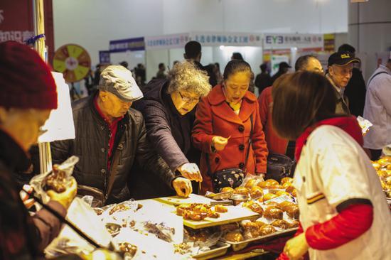 消费者在食品展柜品尝。