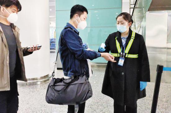 航班的登机口,工作人员为旅客测量体温。