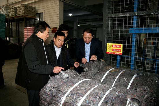 大连民善环保科技有限公司总经理韩永超为市慈善总会执行会长王胜利、副会长周建新介绍旧衣物加工处理过程