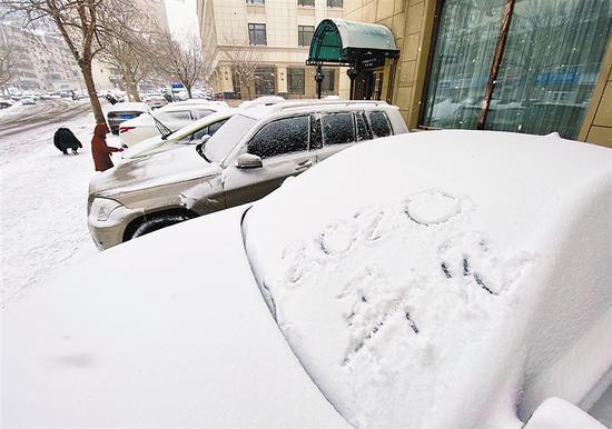 """大连迎来2020年最后一场雪,市区内银装素裹冬意盎然。一个路人在被白雪覆盖的车身上写下""""2020,再见""""的字样。大连新闻传媒集团记者钟启钢 摄"""
