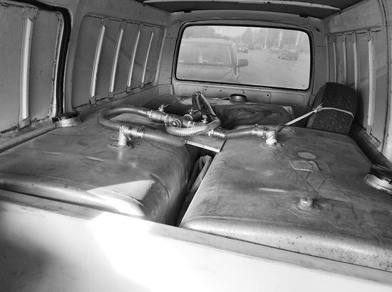 """三个金属箱里装有约550升的汽油,还发现一些印有""""92号汽油送货上门""""的名片。"""