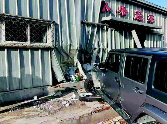 肇事车将市场的大门撞出一个大洞,门内的水果摊被撞散了,拖车最终将肇事车拖走。