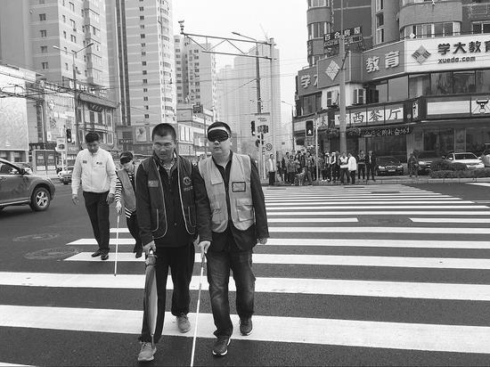 公益活動中,健全人戴著眼罩,借助盲杖過馬路