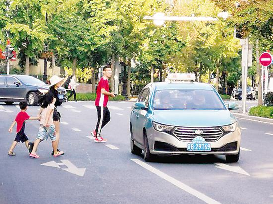 大人领着小孩横穿马路。
