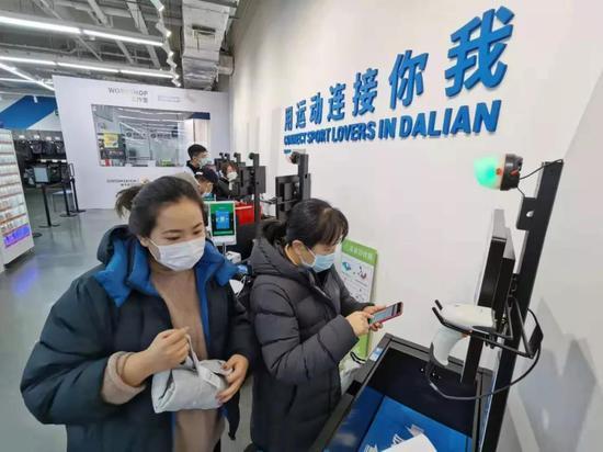 △大连的商场也恢复了营业,顾客在自动收款机付款