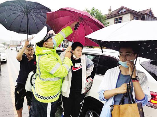 大雨中,坚守在中考考场外的交警。