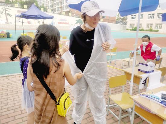 两个女儿帮王晶穿上防护服。