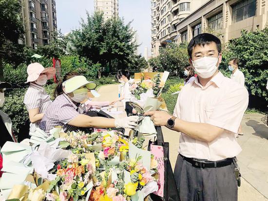 拿到了欢迎的鲜花,居民很开心。