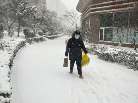 ▲王超冒雪为居家隔离居民送生活物资