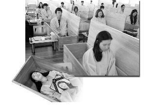 """▲参加""""葬礼""""的员工躺进棺材,抱着自己的""""遗像""""。棺材盖上后,在一片黑暗中,他们会有10分钟安静地思考人生的意义。"""