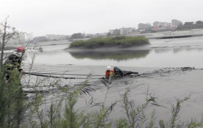 消防员对被困泥潭的老人展开救援。